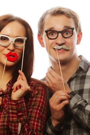 people, party, love and leisure concept - lovely couple holding party glasses and mustaches on stick
